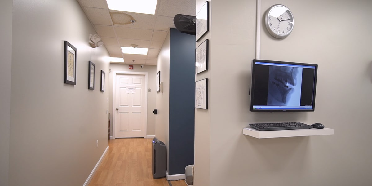 hallway in dental office with wood floors and beige and navy walls