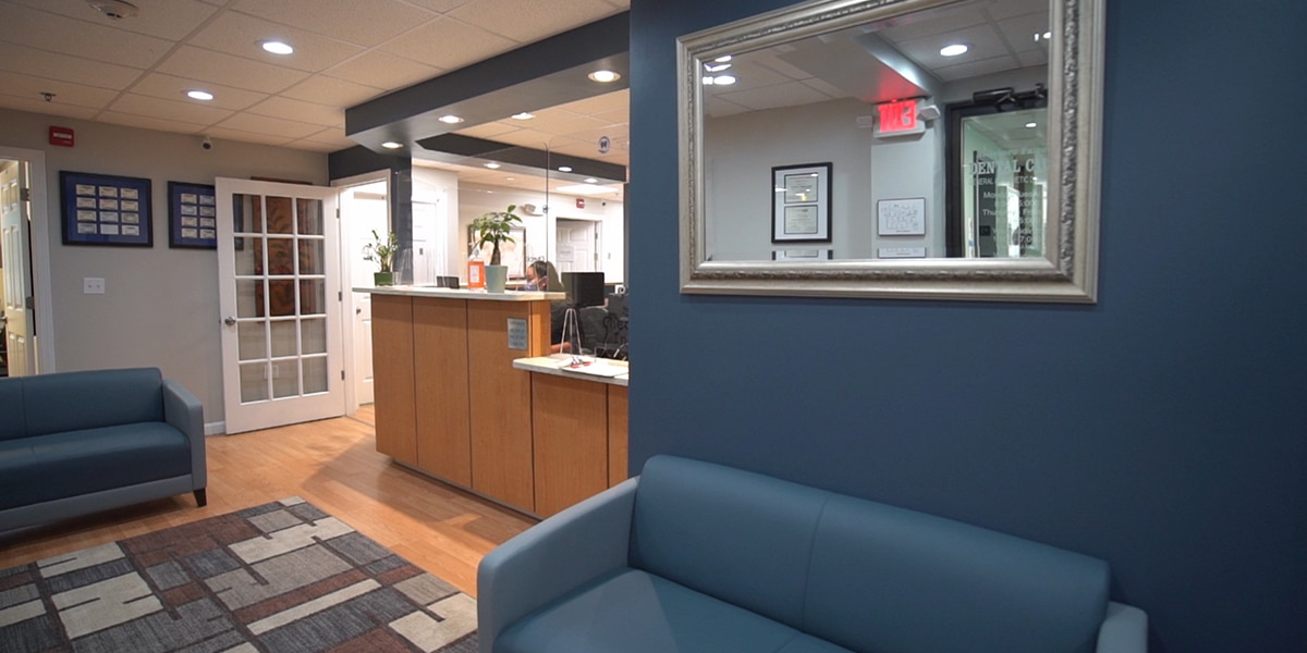 dental reception desk and waiting room with navy couches